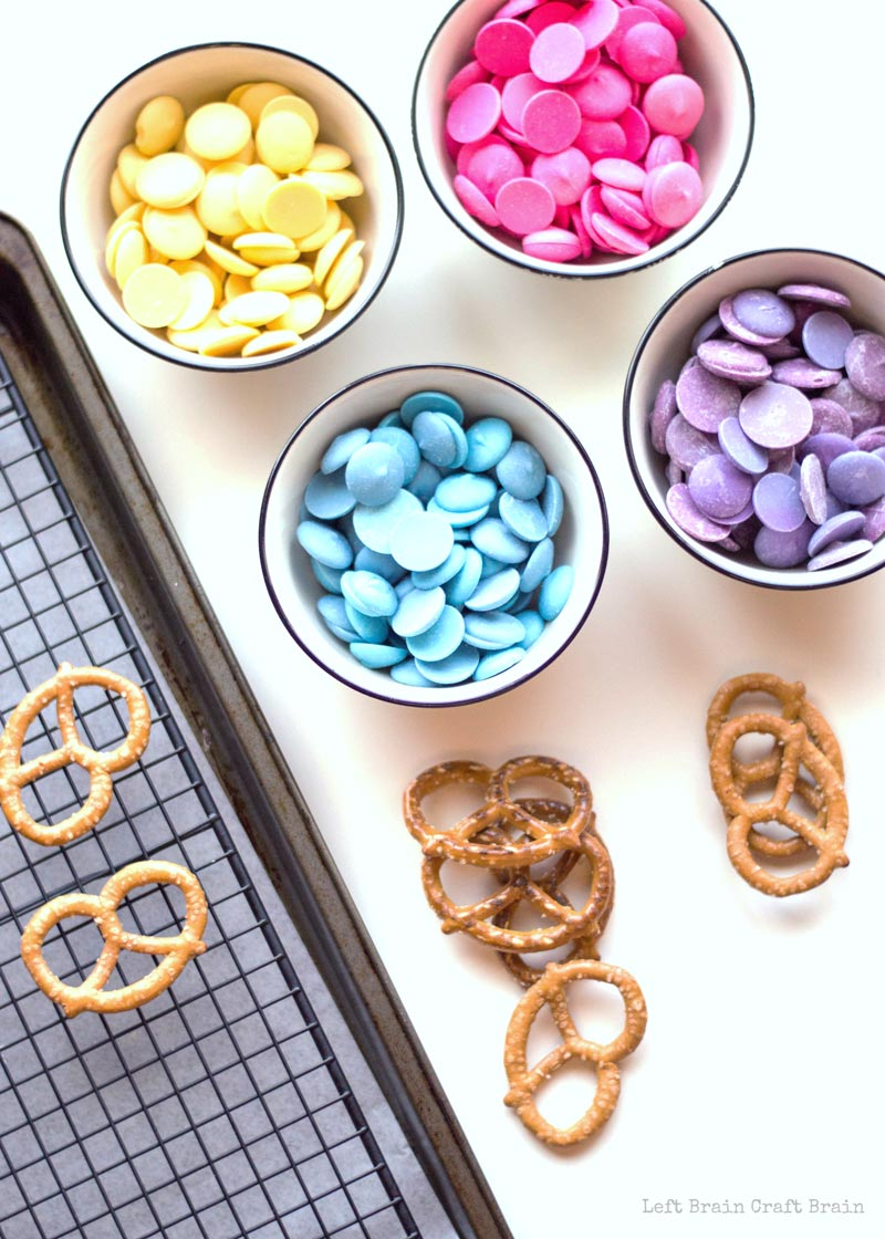 candy melts in yellow, pink, purple, and blue and pretzels on wire rack