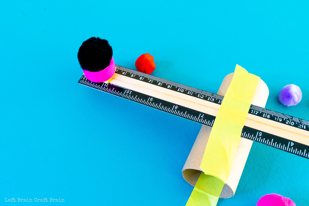 closeup of pom pom on ruler end of catapult
