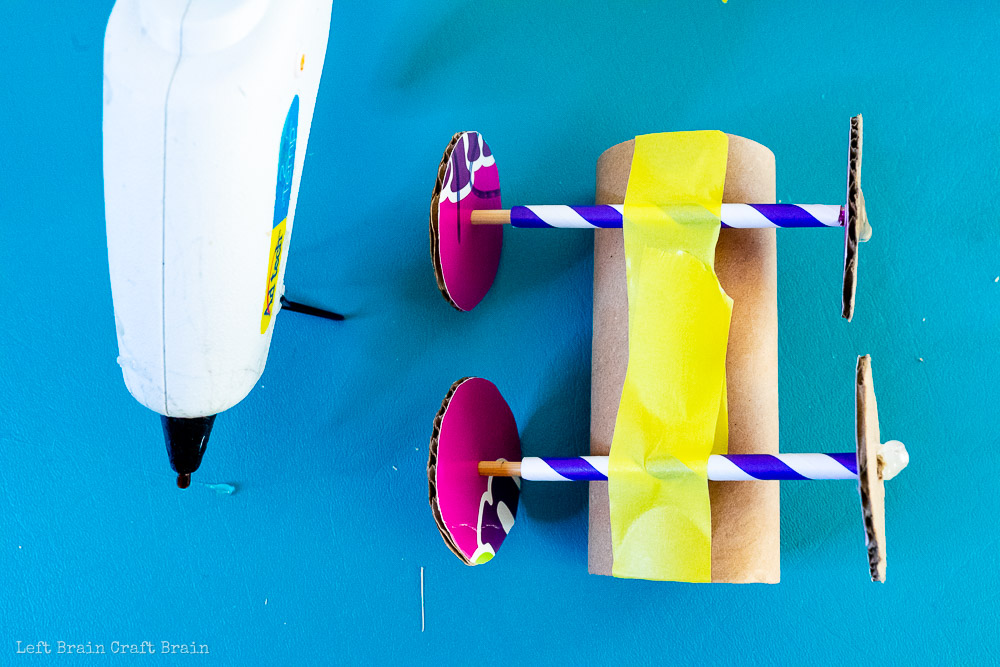 glue together the wheels and axles of the toilet paper roll balloon car