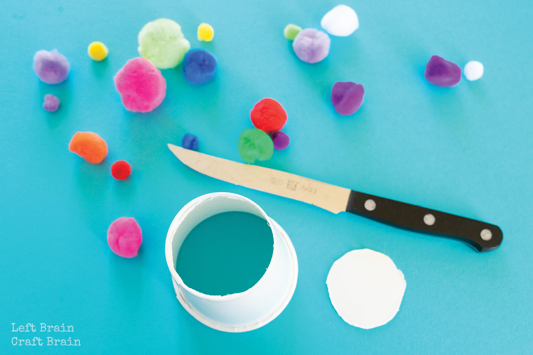pom pom shooter paper cup with hole in it and knife with pom poms on blue
