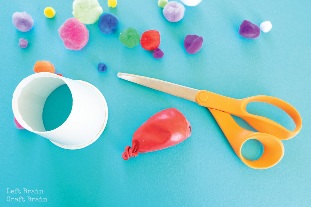 pom pom shooter paper cup with hole in it and balloon with end cut off with pom poms on blue