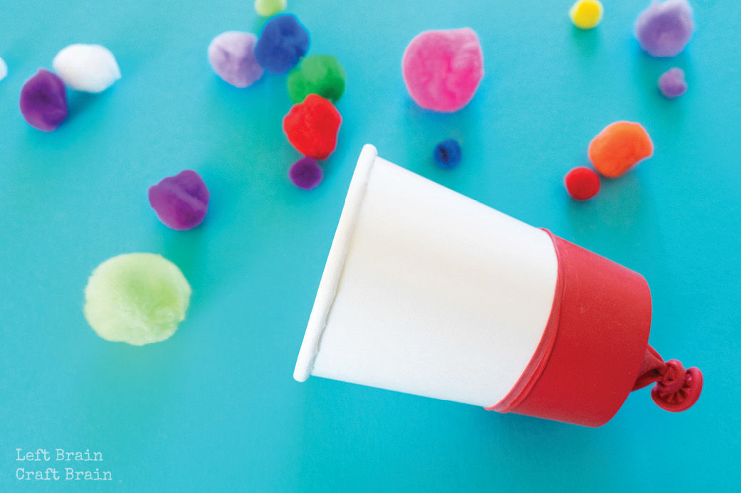 paper cup with balloon on it with pom poms on blue