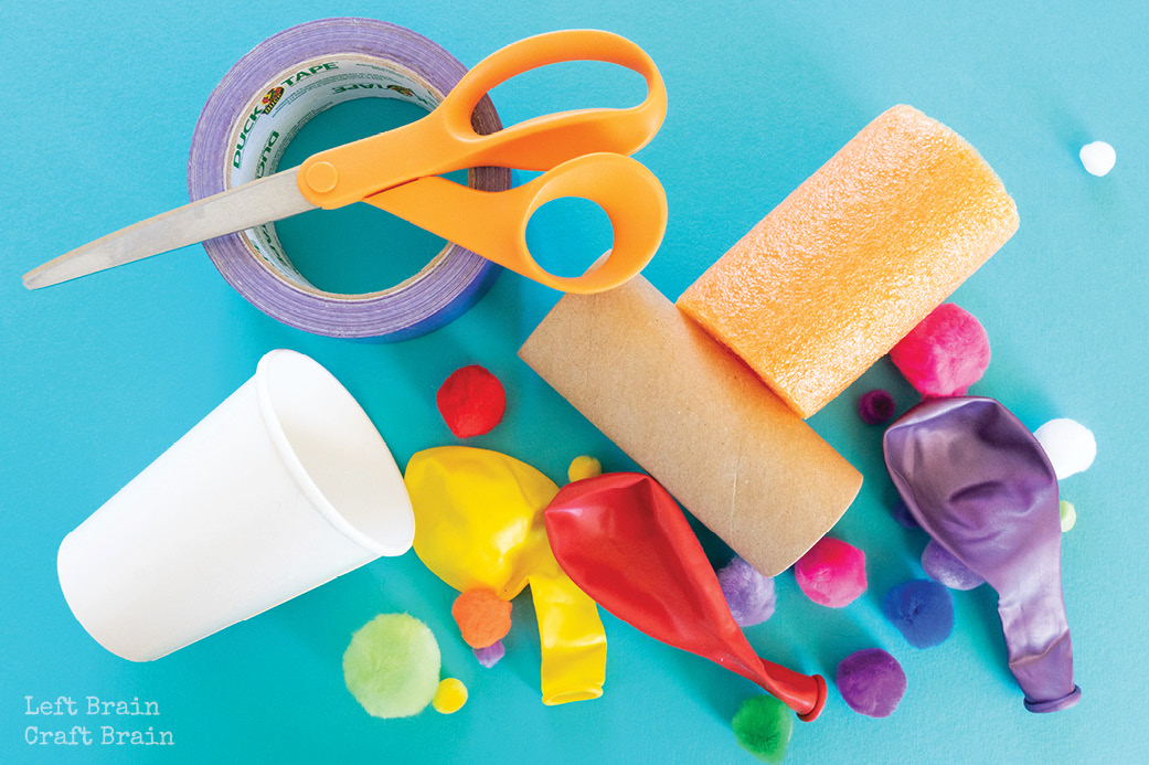 pom pom shooter supplies pom poms  balloons paper cup toilet paper roll scissors duct tape on blue
